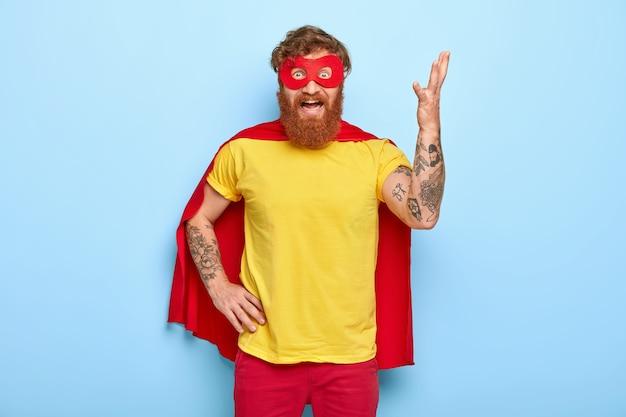 Geïrriteerde superheld heft arm op en gebaart van ergernis, heeft veel werk