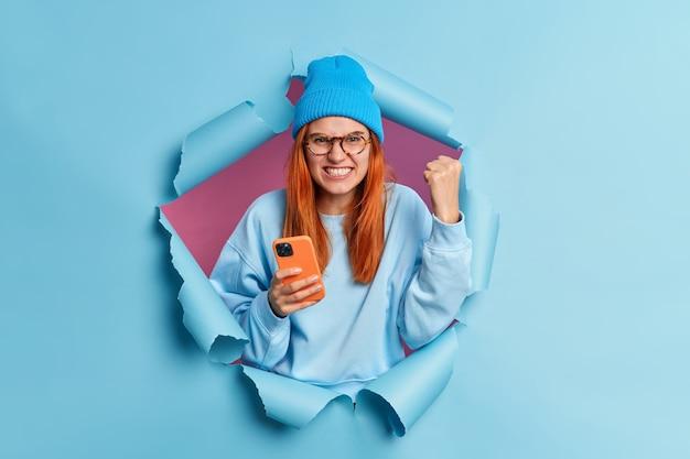 Geïrriteerde tiener klemt zijn tanden op steekt vuist van woede uit drukt negatieve emoties uit, geïrriteerd omdat de smartphone-app niet werkt, kan het noodzakelijke bestand niet downloaden heeft natuurlijk rood haar breekt door papiermuur