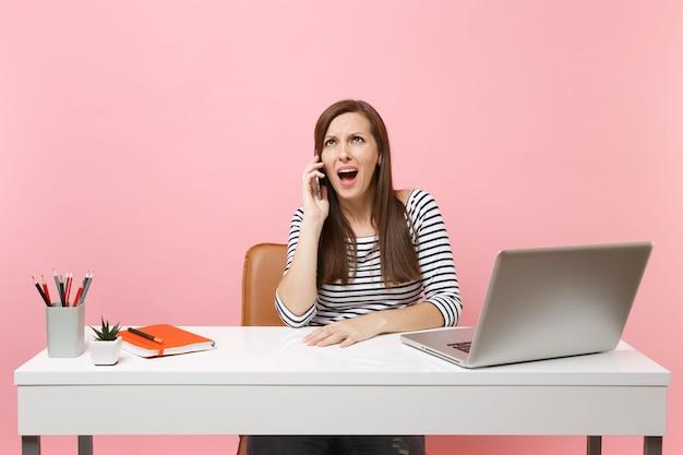Geïrriteerde vrouw in casual kleding praten op mobiele telefoon zittend werken aan project op kantoor met pc-laptop geïsoleerd op pastel roze achtergrond. prestatie zakelijke carrière concept. ruimte kopiëren.