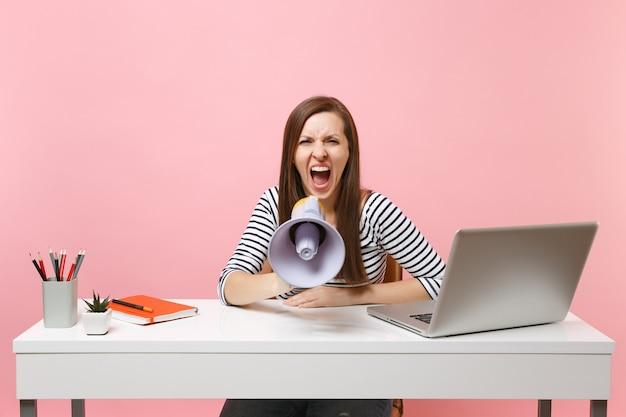 Geïrriteerde vrouw schreeuwt in megafoon terwijl ze zit en werkt aan een project op kantoor met pc-laptop