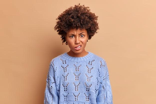 Geïrriteerde vrouw tuitjes lippen en kijkt met geërgerde uitdrukking aan de voorkant draagt casual gebreide blauwe trui hoort iets dat haar woedend maakt geïsoleerd over beige studiomuur