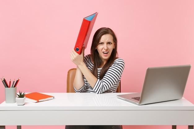 Geïrriteerde vrouw verstopt zich achter rode map met papieren document dat aan project werkt terwijl ze op kantoor zit met laptop geïsoleerd op pastelroze achtergrond. prestatie zakelijke carrière concept. ruimte kopiëren.