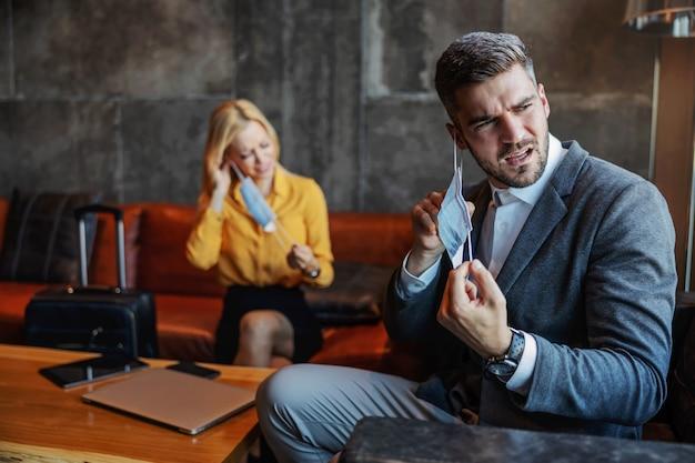 Geïrriteerde zakenmensen halen hun beschermmasker van hun gezicht na een meerdaagse vergadering in een overdekte kantoorruimte. ze zijn woedend over de coronavirus-pandemie blijf gezond covid19-situatie