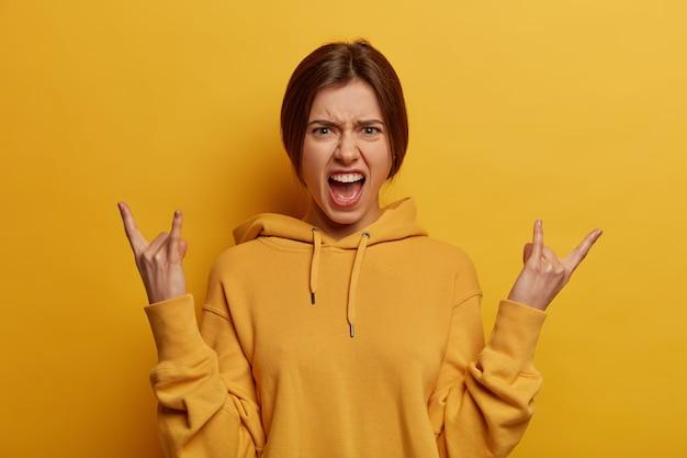 Geïrriteerde, zorgeloze, gekke jonge vrouw schreeuwt en voelt zich opgewonden, maakt rock n roll-gebaar, wordt wild terwijl luide muziek luistert