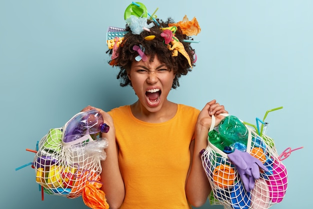 Geïrriteerde zwarte jonge vrouw verzamelt plastic afval, houdt haar mond open, houdt netzakken met afval vast, drukt negatieve emoties uit, eist de natuur, recyclet afval. probleem van de omgeving
