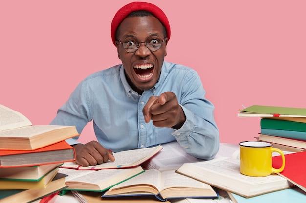 Geïrriteerde zwarte man wijst met wijsvinger naar baas, heeft ruzie over werkprobleem, draagt modieuze rode hoed en shirt