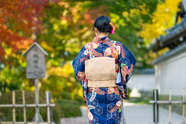 Geisha's meisje draagt japanse kimono onder rode houten tori gate bij fushimi inari shrine in kyoto,