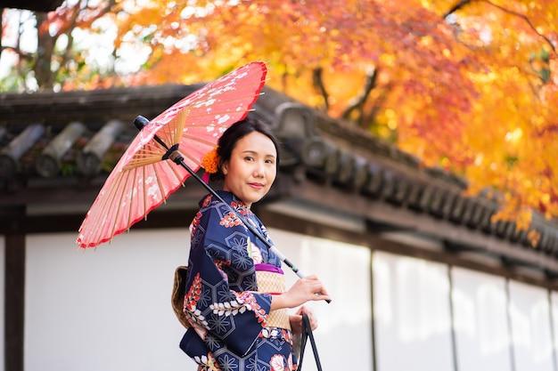 Geisha'smeisje die japanse kimono dragen onder rode houten tori gate