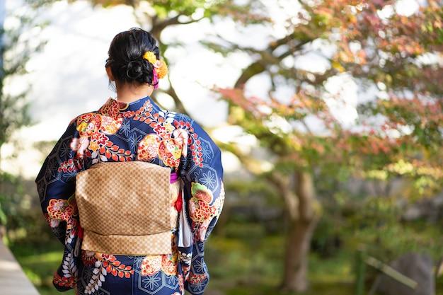 Geishameisje die japanse kimono dragen onder rood houten tori gate bij fushimi inari shrine in kyoto, kimono