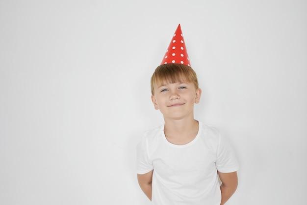 Geïsoleerd beeld van een gelukkige schattige preteen jongen met blond haar, verlegen, hand in hand achter de rug en lachend, zijn verjaardag vierend, wit t-shirt en rode kegel hoed dragen