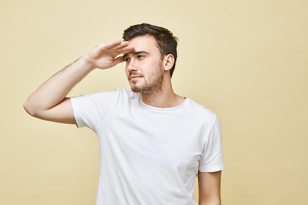 Geïsoleerd beeld van knappe jonge man met stoppels die de hand op zijn voorhoofd houdt en ogen dichtknijpt, bedachtzaam in de verte kijkend, proberend iets ver weg te zien, met zichtproblemen