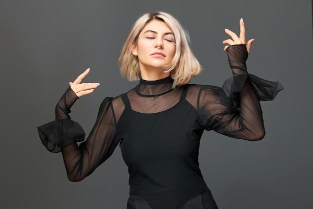 Geïsoleerd beeld van knappe, prachtige jonge blonde vrouw, bewegende handen afgestemd op muziek tijdens concert of optreden, feesten met vrienden, genieten van vrijheid, met vrolijke vrolijke gezichtsuitdrukking