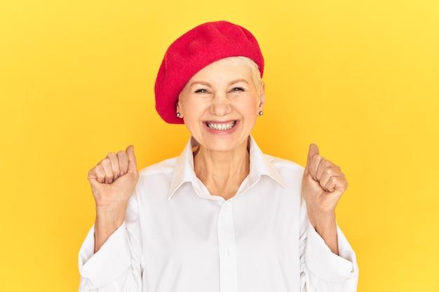 Geïsoleerd beeld van modieuze positieve vrolijke rijpe franse vrouw, gekleed in een wit overhemd en een rode motorkap met gebalde vuisten en breed glimlachend, dolblij met goed nieuws, ja opgewonden schreeuwend