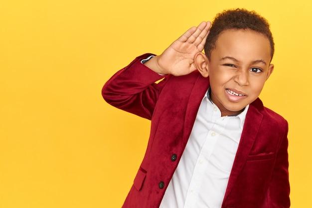 Geïsoleerd beeld van nieuwsgierige nieuwsgierige afro-amerikaanse schooljongen die afluistert, vertrouwelijk geheim gesprek afluistert, hand aan zijn oor houdt