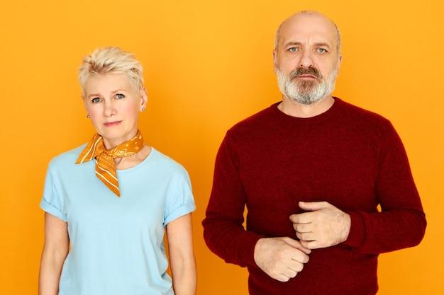 Geïsoleerd beeld van ongelukkig senior man met dikke baard staan naast zijn mooie vrouw camera kijken met droevige gezichtsuitdrukkingen, boos gefrustreerd gevoel na gevecht. mensen en relaties