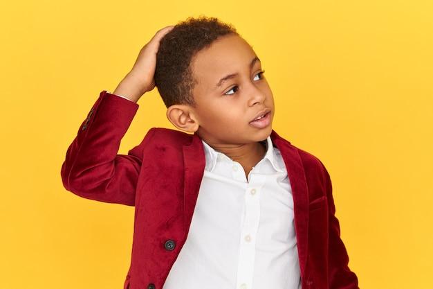Geïsoleerd beeld van schattige verwarde afro-amerikaanse schooljongen opzoeken met verbaasde perplex gezichtsuitdrukking krabben hoofd, vergat huiswerk te doen, in verlegenheid gebracht.