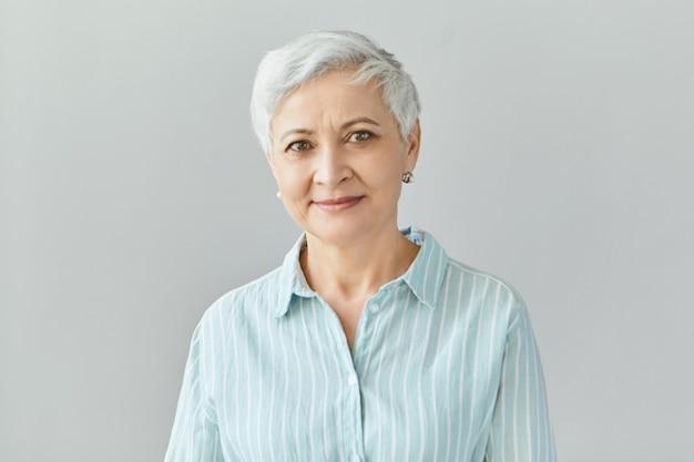 Geïsoleerd beeld van vriendelijke knappe europese zakenvrouw met pixie grijs haar glimlachend zelfverzekerd, blij met de werkresultaten van haar team, gekleed in formeel gestreept overhemd