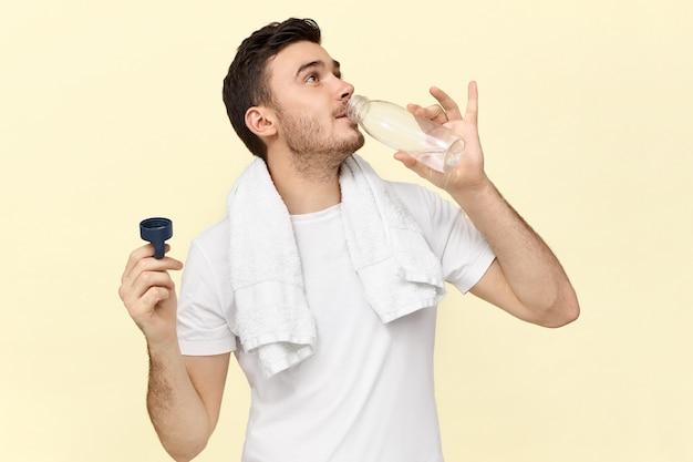 Geïsoleerd beeld van zelfverzekerde knappe jongeman met handdoek om de nek die plastic fles vasthoudt, zichzelf verfrist na lichamelijke inspanning in de sportschool, gretig water drinkt, wit t-shirt draagt
