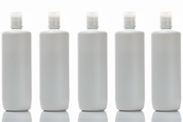 Geïsoleerd duidelijk wit plastic flessenmalplaatje dat zich op een rij bevindt.