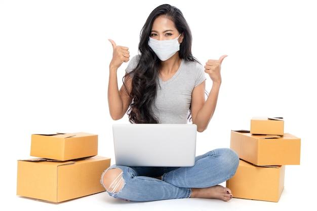 Geïsoleerd een aziatische vrouw zit op de grond met veel pakketbakken aan de zijkant