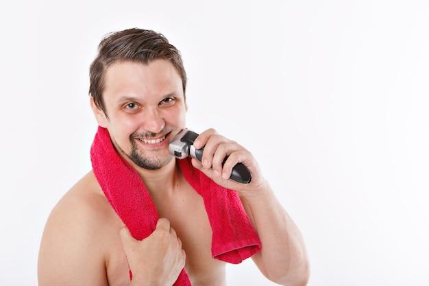 Geïsoleerd: een man scheert zijn stoppels. de man maakt zijn baard schoon met een elektrisch scheerapparaat. ochtendbehandelingen in de badkamer. rode handdoek om haar nek. kopieer ruimte