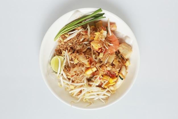 Geïsoleerd gebakken noodle thaise stijl met garnalen en zeevruchten thailand call pad thai, roergebakken noodle thaise stijl op wit.