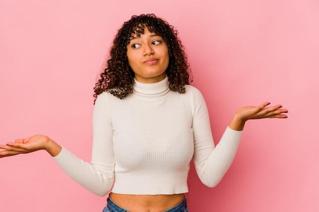 Geïsoleerd jonge afro vrouw twijfelende en schouders ophalen in vragend gebaar