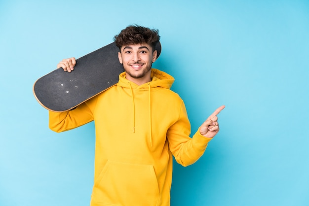 Geïsoleerd jonge arabische skater man glimlachend en opzij wijzend, iets op lege ruimte laten zien.