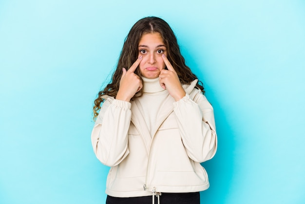 Geïsoleerd jonge blanke vrouw met krullend haar huilen, ongelukkig met iets, pijn en verwarring concept.