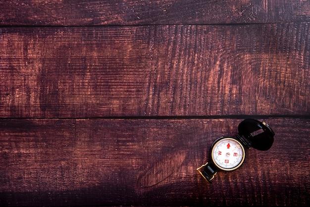 Geïsoleerd kompas op een bruine oude houten lijst
