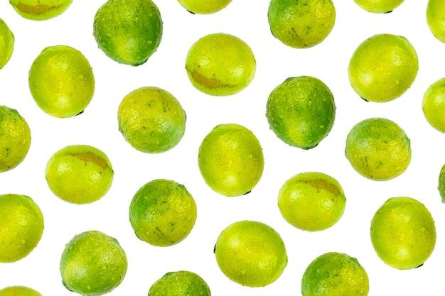Geïsoleerd limoenpatroon of behang op witte achtergrond. zomer concept van verse rijpe hele limoen fruit geschoten van bovenaf