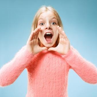 Geïsoleerd op blauw casual tiener meisje schreeuwen in de studio