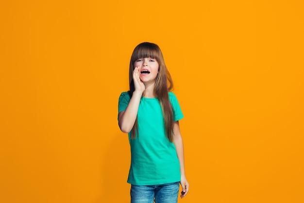 Geïsoleerd op geel casual tiener meisje schreeuwen in de studio