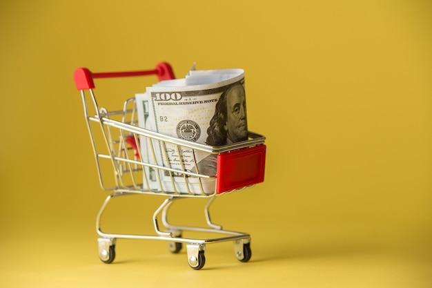 Geïsoleerd op geel winkelwagentje gevuld met thaise munten.