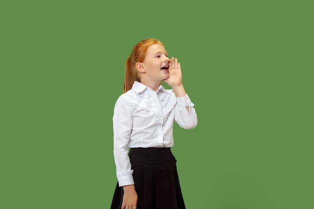 Geïsoleerd op groen casual tiener meisje schreeuwen in de studio