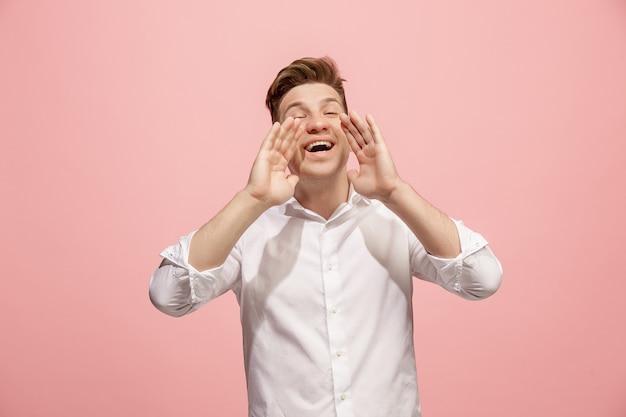 Geïsoleerd op roze casual jongeman schreeuwen in de studio