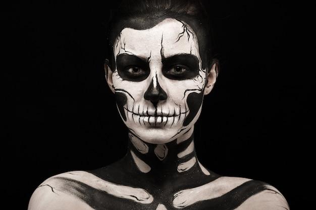 Geïsoleerd op zwart, close-up foto, mooie jonge brunette kaukasische vrouw met schedel body art, grijze ogen, serieus