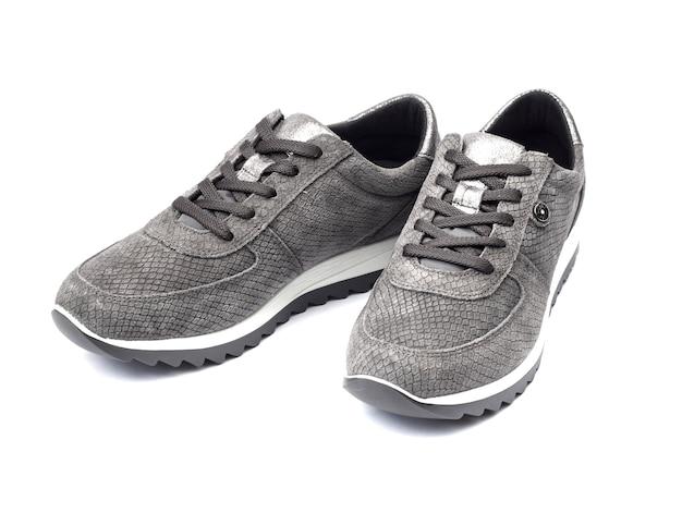 Geïsoleerd paar nieuwe grijze vrouwelijke suède tennisschoenen