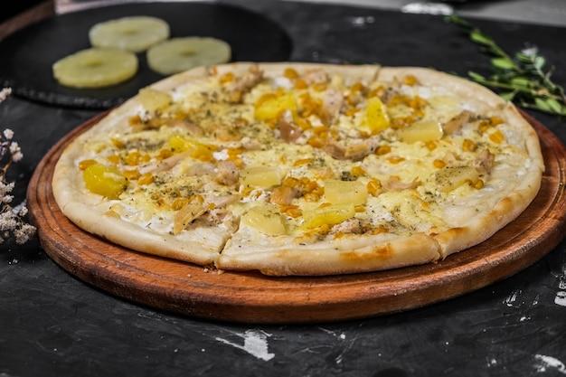 Geïsoleerd pizza met kip en ananas op een houten bord en op een donkere ondergrond