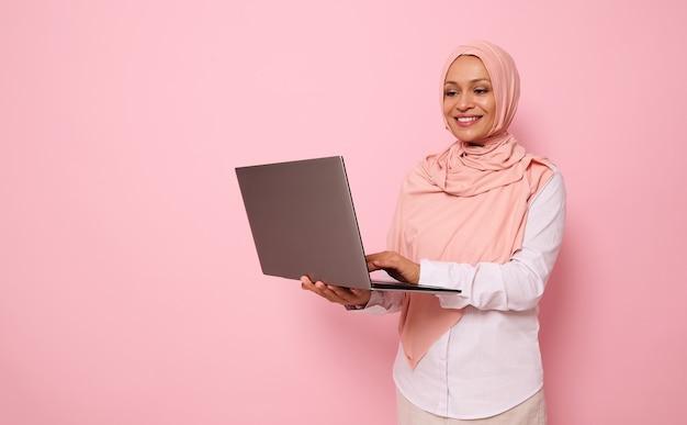 Geïsoleerd portret op roze achtergrond met ruimte voor tekst van een succesvolle moslim mooie vrouw van middelbare leeftijd van midden-oosterse etniciteit die hijab draagt en gekleed slimme casual outfit die op laptop werkt