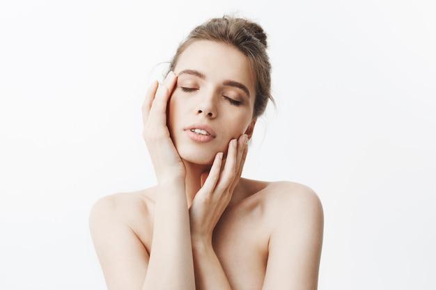 Geïsoleerd portret van aantrekkelijk ark-haired europees studentenmeisje met knotkapsel en naakte schouders die hoofd met handen houden, die gezichtsuitdrukking met gesloten ogen hebben ontspannen.