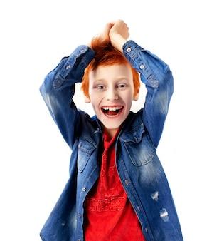 Geïsoleerd portret van een emotioneel verraste ondeugende gelukkige tienerjongen op een witte achtergrond met rood haar red