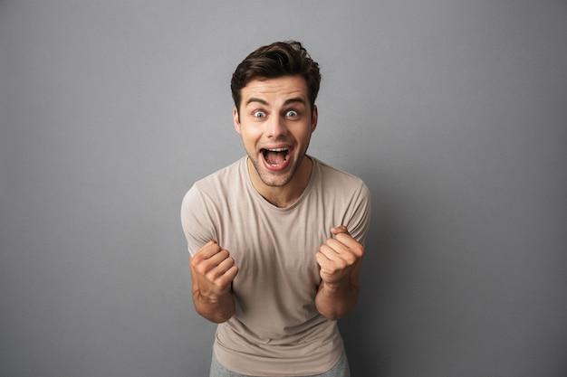 Geïsoleerd portret van een gelukkige jonge mens in t-shirt