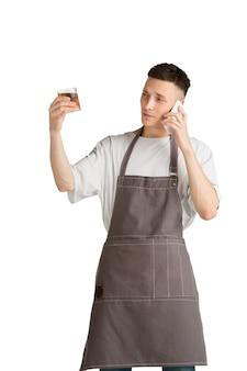 Geïsoleerd portret van een jonge mannelijke blanke barista in bruine schort