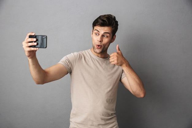 Geïsoleerd portret van een vrolijke jonge mens in t-shirt