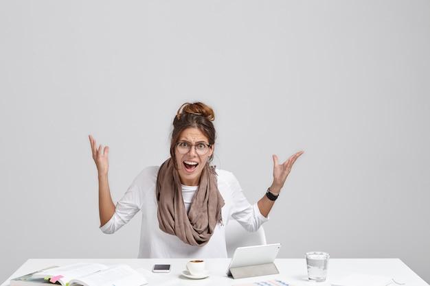 Geïsoleerd portret van geïrriteerde ongelukkige jonge vrouwelijke ondernemer gekleed in vrijetijdskleding actief gebaren en uitroepen,