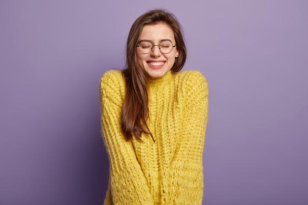 Geïsoleerd portret van gelukkige vrouw heeft brede glimlach, sluit ogen, voelt plezier van goed compliment, draagt bril en gele trui, staat over paarse muur. positieve emoties en gevoelens concept