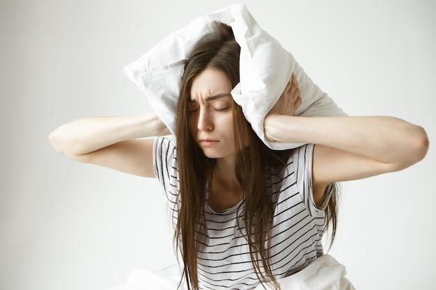 Geïsoleerd portret van gestreste jonge brunette vrouw die gestreepte pyjama draagt die oren bedekt met een wit kussen, gefrustreerd voelt omdat ze 's nachts niet in slaap kan vallen vanwege haar snurkende echtgenoot