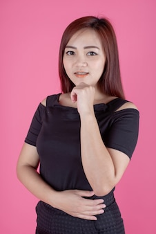 Geïsoleerd portret van glimlachende mooie jonge vrouw in het minikleding stellen