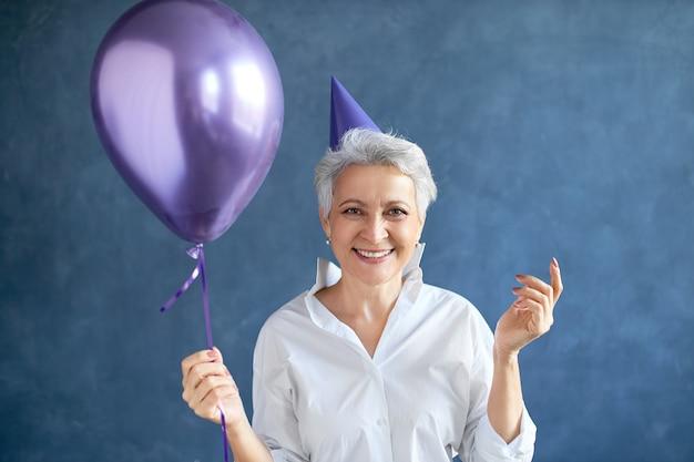 Geïsoleerd portret van succesvolle rijpe onderneemster met kort grijs haar die zich voordeed op blinde muur met heliumballon